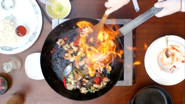 Fresh seafood in the frying pan on fire