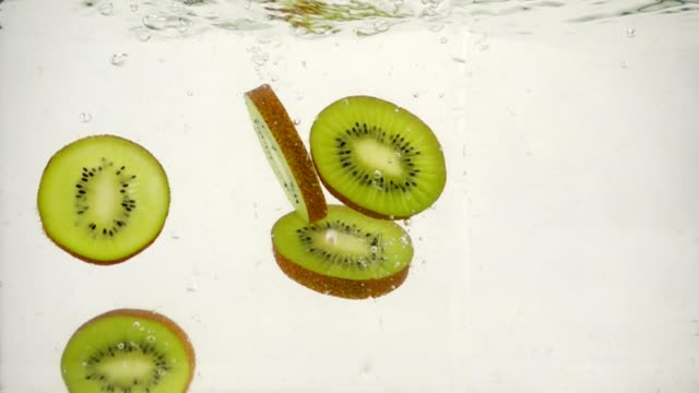 vídeos de stock e filmes b-roll de fresh slices of kiwi fruit with splashes falling into a water on a white background close-up - kiwi