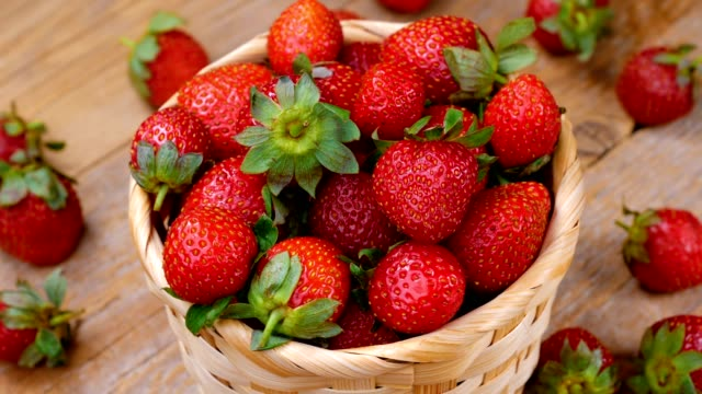vídeos de stock e filmes b-roll de fresh strawberries in basket spinning on wooden table - strawberry