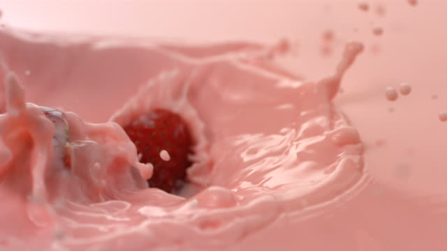 Fresh strawberries splashing into pink cream, slow motion video