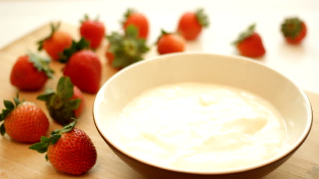 Fresh strawberries splashing into yogurt video