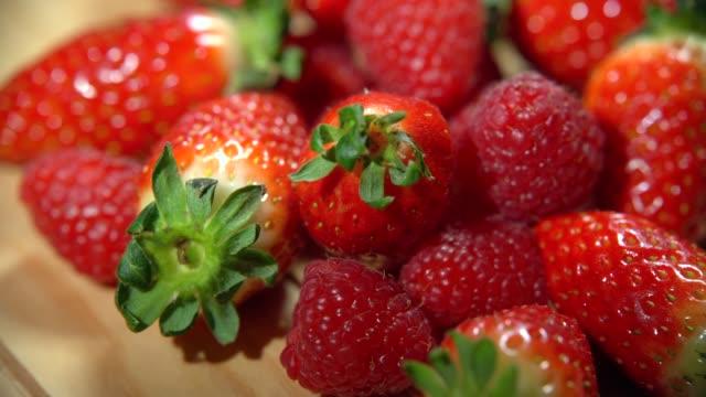 färsk jordgubb och hallon på träets bakgrund. hälsosam mat ekologisk näring. 4k - hallon bildbanksvideor och videomaterial från bakom kulisserna