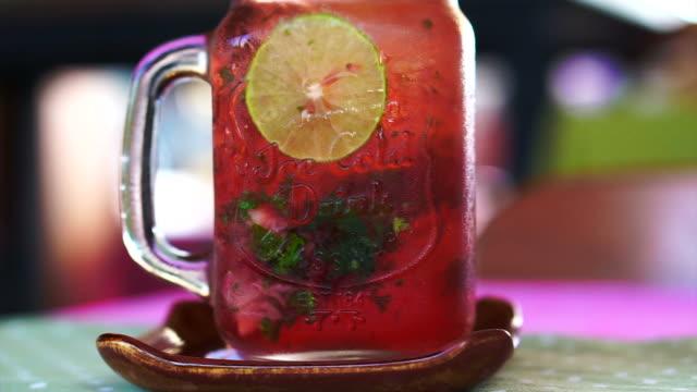 vídeos de stock e filmes b-roll de fresh summer drink red strawberry, lemon and mint serve in mason jar - limonada tradicional