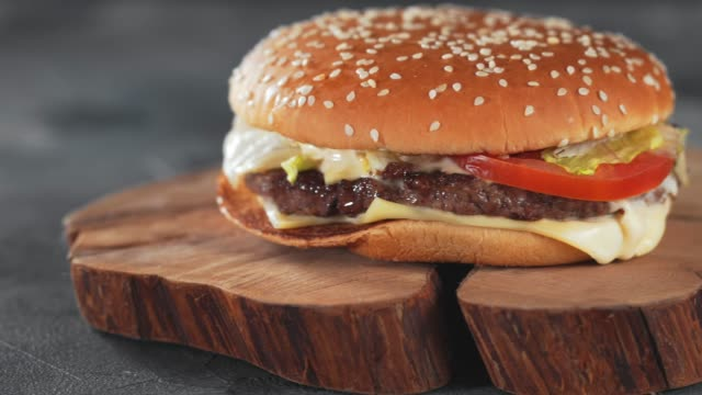 Fresh tasty homemade beef burger on wooden plate on table, panoramic slide shot video