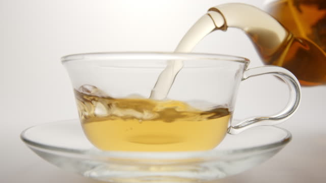 SLOW MOTION: Fresh tea flows in a tea cup from a teapot video