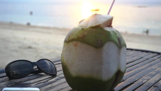 vídeos de stock e filmes b-roll de fresh thai coconut cocktail, sunglasses lying on wooden table at tropical beach during amazing sunset. travel vacation concept. slow motion. thailand. 1920x1080 - home decor boho