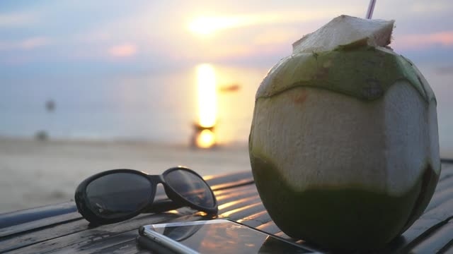 vídeos de stock e filmes b-roll de fresh thai coconut cocktail, sunglasses, mobile phone lying on wooden table at tropical beach during amazing sunset. travel vacation concept. slow motion. thailand. 1920x1080 - home decor boho