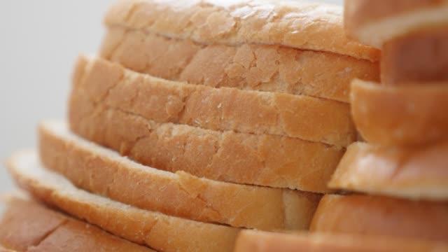 新鮮なトーストパンの部分は、食品の背景スローチルト4kをクローズアップ - 食パン点の映像素材/bロール