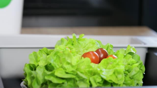 Fresh tomato falling down on lettuce in bowl