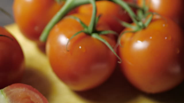 Fresh Tomatoes and Sliced Tomato. Move left.Dark background.No people. tomato salad stock videos & royalty-free footage
