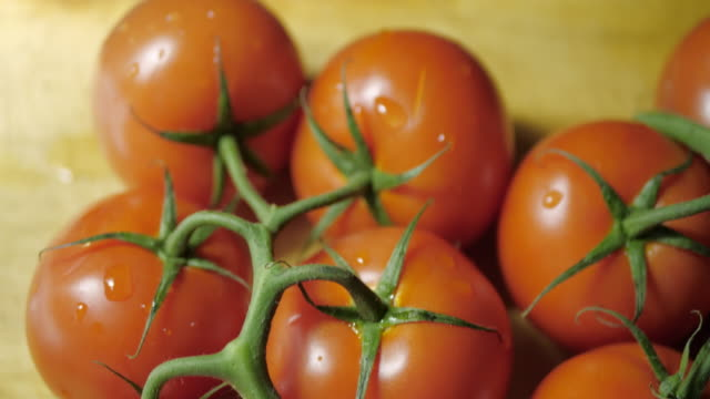 Fresh tomatoes on a cutting board. The camera moves down. Dark background .No people.Transition to the dark. tomato salad stock videos & royalty-free footage