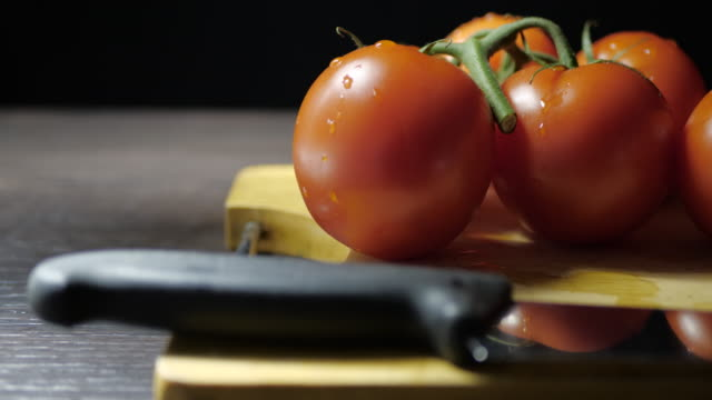 Fresh tomatoes on a cutting board with a knife. The camera moves smoothly and slowly to the right. Dark background No people. tomato salad stock videos & royalty-free footage