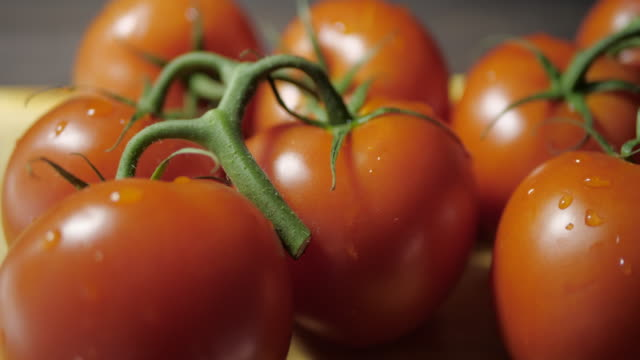 Fresh tomatoes. The camera moves smoothly and slowly to the left. Dark background No people.Close-Up. tomato salad stock videos & royalty-free footage