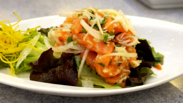 Fresh uncooked fresh salmon with salad vegetable in white dish on wood table by motion. video