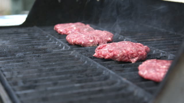 vídeos de stock e filmes b-roll de fresh uncooked pink local ground beef hamburgers cooking for dinner on the grill in the summer - cru