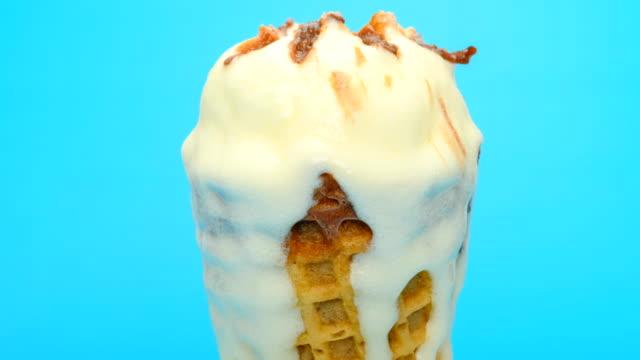 vidéos et rushes de crème glacée fraîche saveur de vanille cône fondre et est tombé timelapse sur backgroud bleu - vanille
