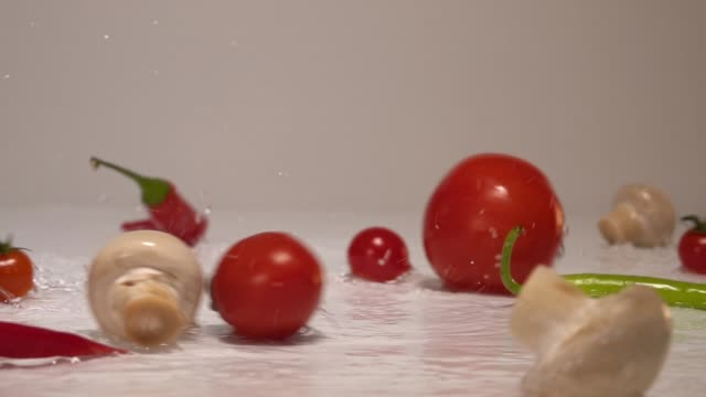 fresh vegetables falling with water in slow motion on white background - vídeo