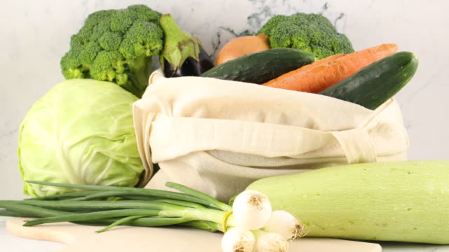 fresh vegetables, onion, carrot, zucchini, broccoli, cabbage, cucumber on shopping bag - aglio cipolla isolated video stock e b–roll
