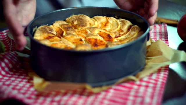Freshly baked apple cake. Closeup. Hands put baked apple pie on table video