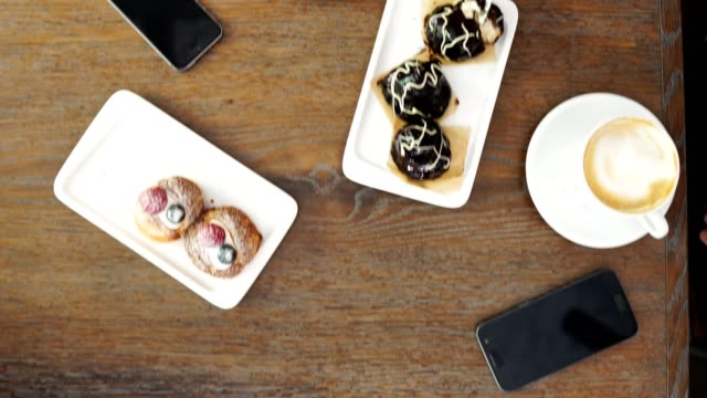 vídeos de stock e filmes b-roll de freshly baked blueberry muffins in a rustic setting with milk and coffee on the table overhead shot with copyspace - top view, dark wood table, empty