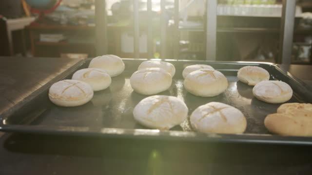 vídeos de stock e filmes b-roll de freshly baked bread buns at home - baking bread at home