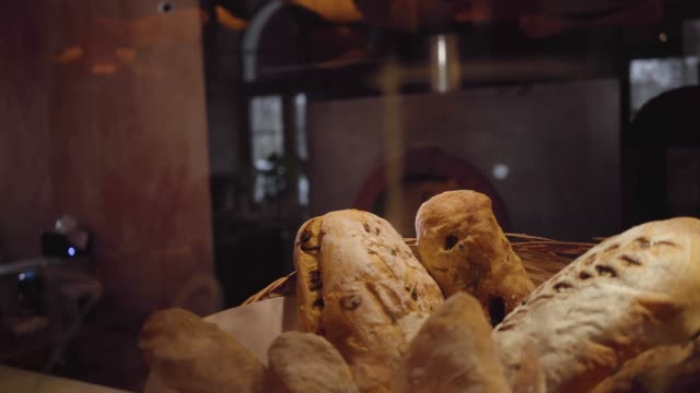 Freshly baked bread lying in the basket in the foreground on the table close up.