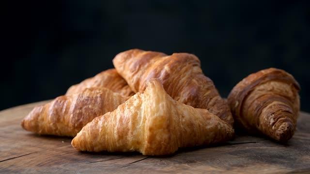 vídeos de stock e filmes b-roll de freshly baked croissants on old wooden table - assado no forno
