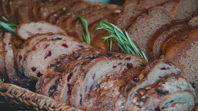 vídeos de stock, filmes e b-roll de pão de grãos recém-cozido cortado em fatias. - rústico