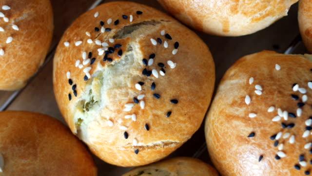 dolly: vari panini da pasticceria appena sfornato con semi di sesamo e girasole - carrellata video stock e b–roll