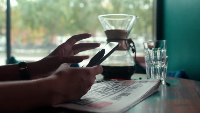 Freshly brewed coffee and a newspaper. Woman with cell phone video