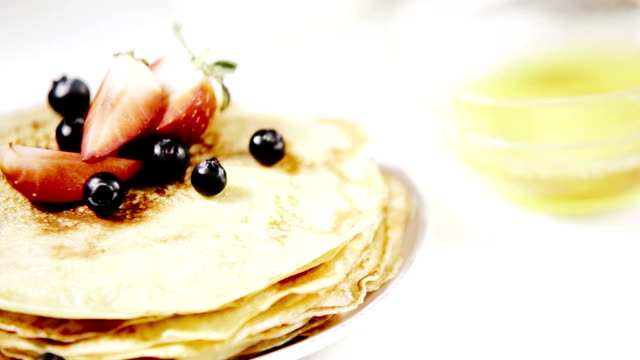 Freshly cooked pancakes with fruit being flavoured with honey video