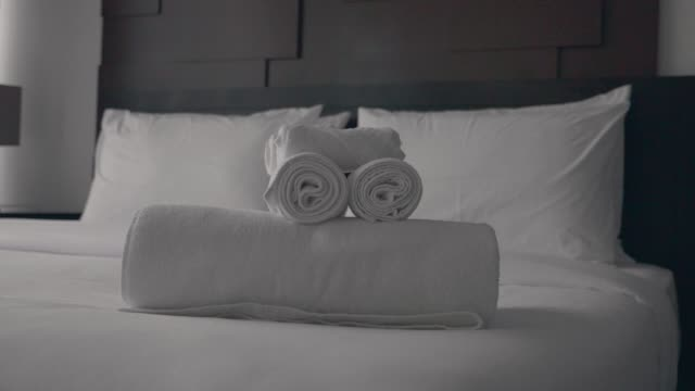 Freshly Laundered Fluffy Towels Freshly laundered fluffy towel rolls on a hotel bed in luxury hotel room with white bedding. Welcome resort decor in slow motion. hotel stock videos & royalty-free footage