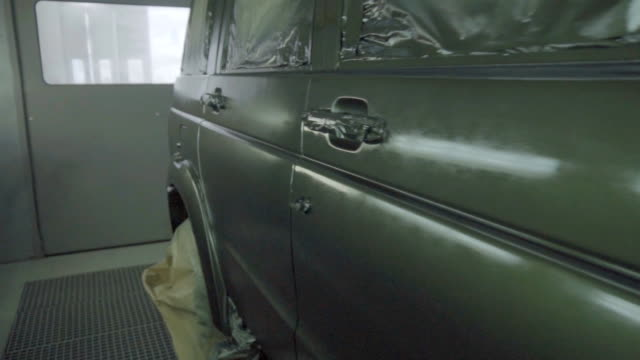 A freshly painted car is in a spray booth. Professional car painting, SUV, slow motion