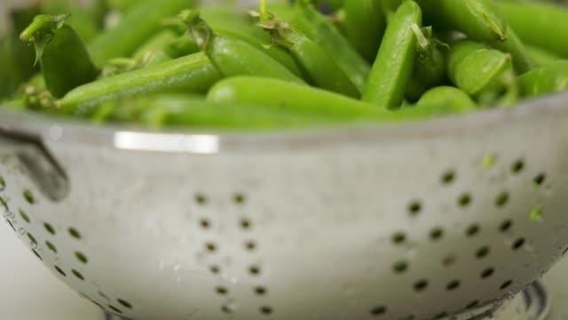 Freshly picked green peas in colander closeup video