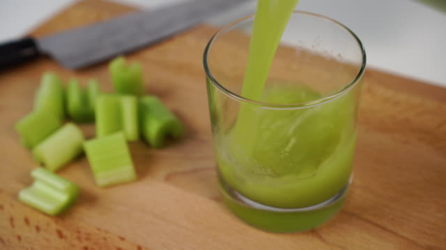 vídeos de stock e filmes b-roll de freshly squeezed celery juice is poured into a glass cup on a wooden cutting board. with a knife and sliced juicy slices - sumo