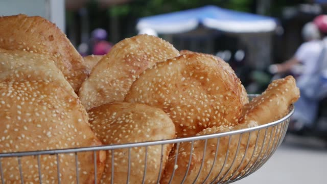Fried buns with sesame seeds in a basket on the market in Vietnam. Closeup Closeup Fried buns with sesame seeds in a basket on the market in Vietnam pickle stock videos & royalty-free footage
