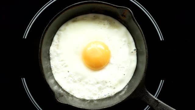 vídeos y material grabado en eventos de stock de huevo frito en un lapso de tiempo de proceso de preparación de sartén de hierro fundido - frito