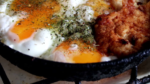 Fried eggs in a pan close up And fried chicken nuggets with spices video