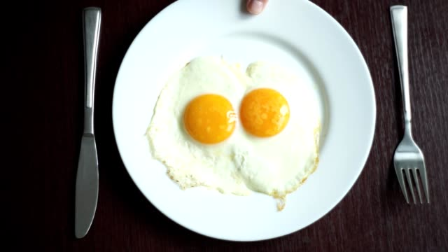 Fried eggs on plate. Putting plate with fried eggs on wooden table Fried eggs on plate. Putting plate with fried eggs on wooden table. Close up white porcelain plate with fried egg. Traditional breakfast meal. Serving breakfast. Breakfast food fork stock videos & royalty-free footage