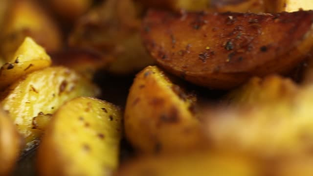 fried in ghee with spices pieces of potatoes - patate video stock e b–roll