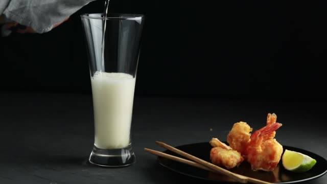Fried Shrimps tempura with lime in black plate and pouring beer in glass on pink or peach concrete surface background. Copy space Seafood tempura dish served japanese or eastern Asia style with chopsticks video