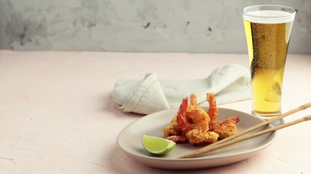 Fried Shrimps tempura with lime in light plate and pouring beer in glass on pink concrete surface background. Copy space Seafood tempura dish served japanese or eastern Asia style with chopsticks video