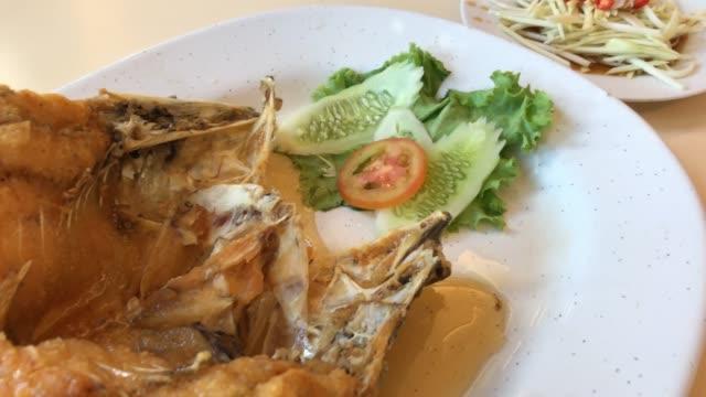 жареная рыба-окунь с рыбным соусом - white background стоковые видео и кадры b-roll