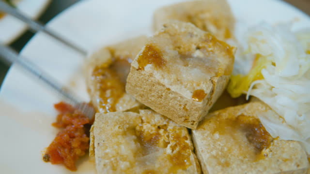 Fried stinky tofu serve on plate with plastic. Famous and iconic fermented tofu of Taiwan video