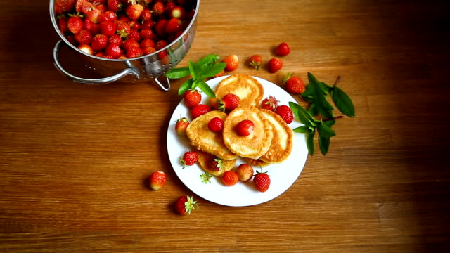 vídeos de stock e filmes b-roll de fried sweet pancakes with ripe strawberries in a plate - christmas cake