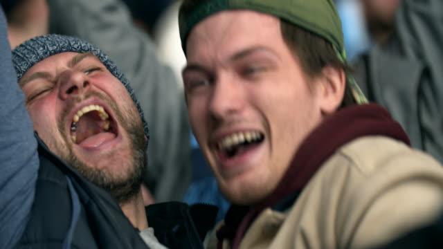 vídeos de stock e filmes b-roll de friend joy game hockey score win closeup fan emotion scream crowd stadium 4k. - soccer supporter portrait