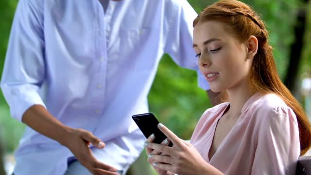 stockvideo's en b-roll-footage met vriend spottende meisje met behulp van mobiele telefoon geobsedeerd met sociaal netwerk, verslaving - kids online abuse