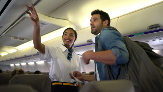 friendly air stewardess gesturing the seat of a young man who puts his bag in over head compartment - wchodzić na pokład filmów i materiałów b-roll