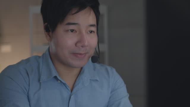デスクトップ コンピュータでヘッドセットを使用したフレンドリーなアジアのカスタマー サービス - オペレーター 日本人点の映像素材/bロール