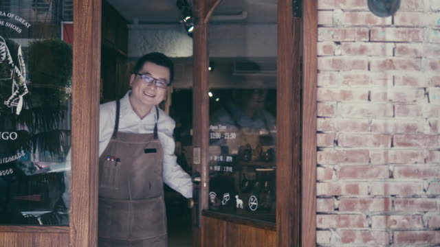 Friendly asian male manager opens shoe shop door and welcomes new customers